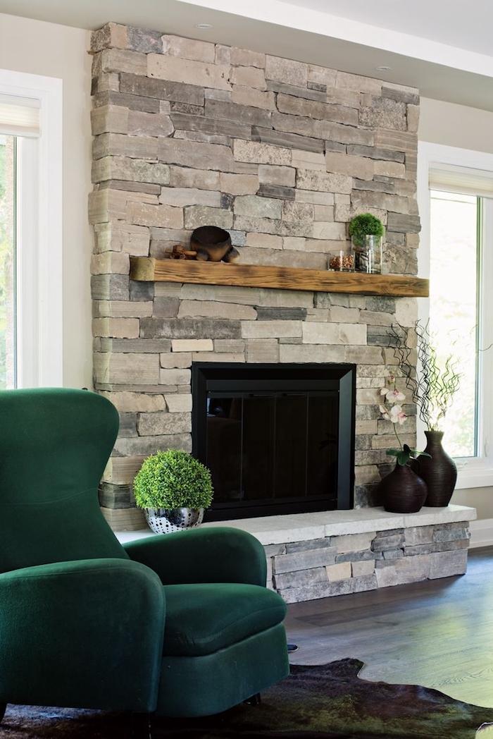 manteau de cheminée décoratif en pierre de parement couvrant le mur et etagere en bois, fauteuil design vert foncé
