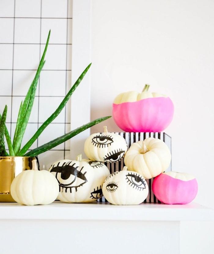 idee deco halloween citrouille décorée de peinture rose et dessin des yeux noirs, deco a faire soi meme terrifiante et élégante