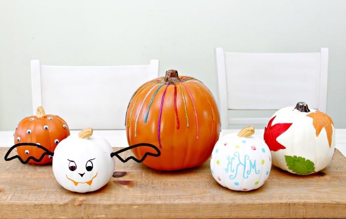 modèles de citrouilles décorées pour la fête d'Halloween avec peinture et feuilles séchées, citrouille blanche à déco visage effrayant