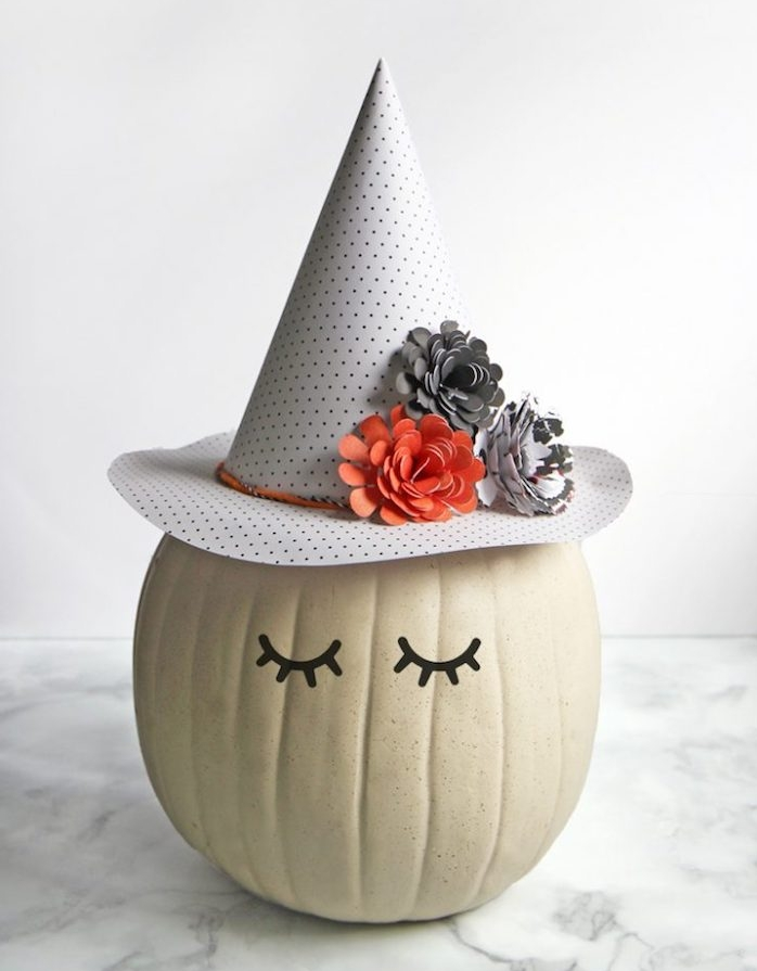 citrouille sorcière fabriqué à partir d une citrouille aux yeux noirs et un chapeau sorcière décorée de fleurs en papier