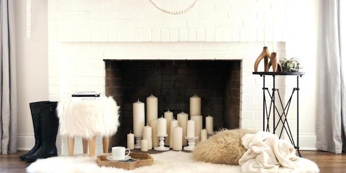 bougies dans foyer cheminée briques blanches avec tabouret à poils et coin cosy dans salon