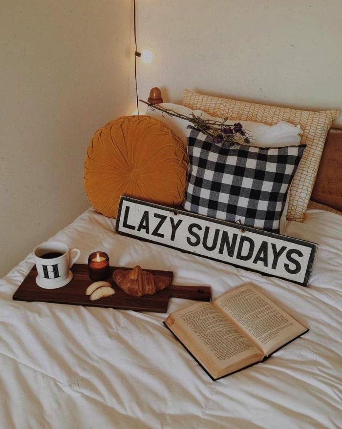 housse de couette cocooning, livre et petit déjeuner avec un café sur le lit, coussin jaune, coussin à carreaux, guirlande lumineuse