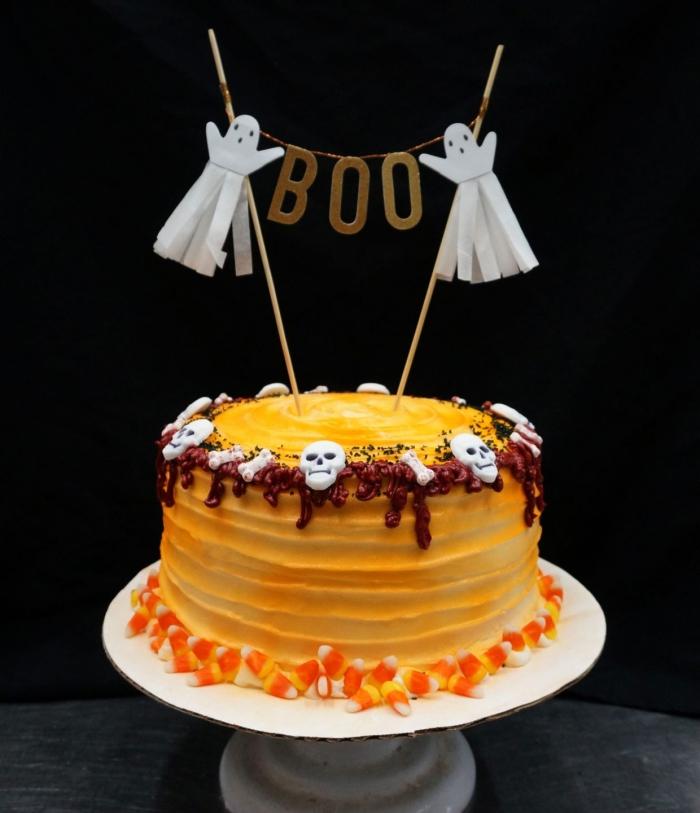 modèle de dessert Halloween facile, recette gâteau aux génoises à la vanille avec ganache orange et déco crânes en sucre