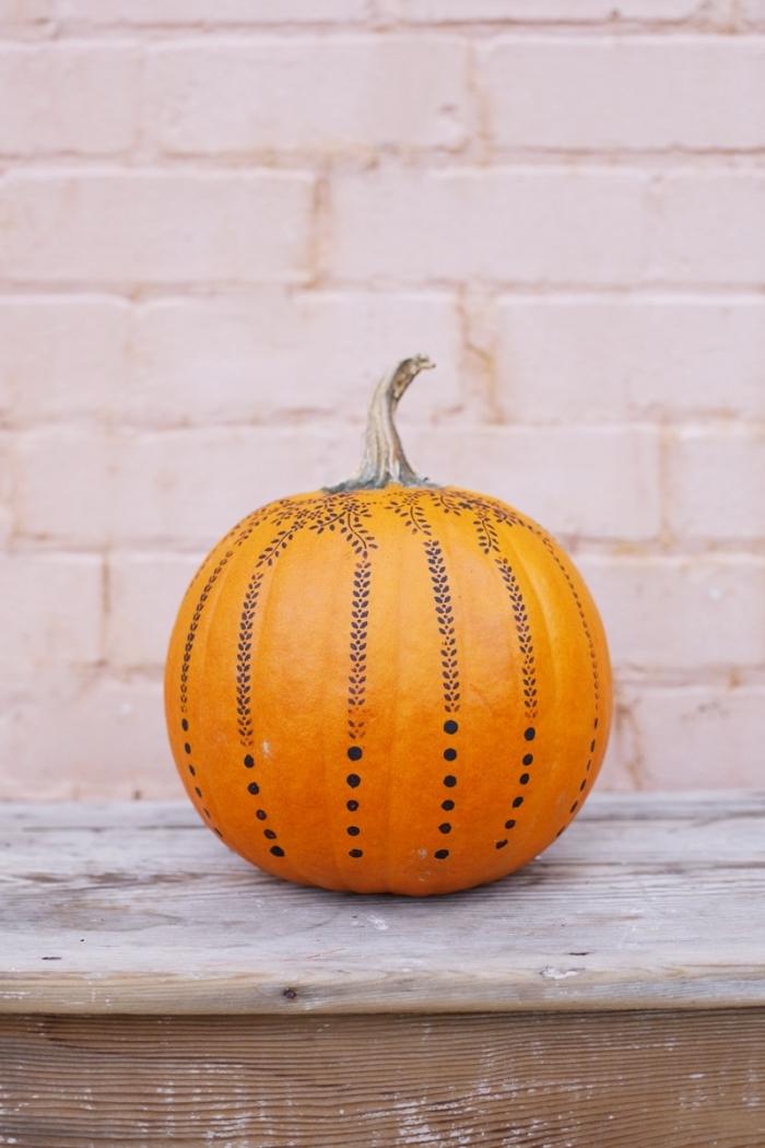 modèle de décoration facile à réaliser sur une citrouille orange, idée comment personnaliser une citrouille Halloween avec feutre noir