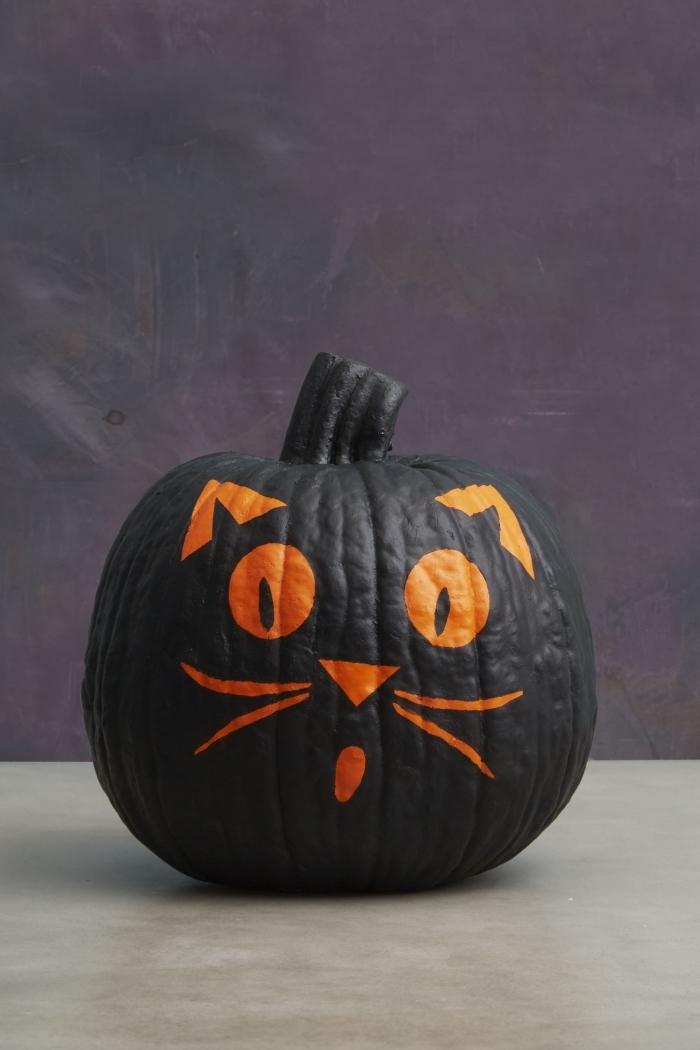 faire une décoration citrouille, modèle de citrouille peinte en noir avec dessin tête de chat, idée comment décorer une citrouille