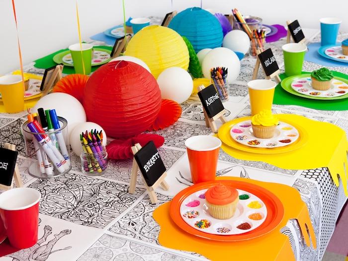 atelier culinaire avec de cupcakes colorées à décorer de billes colorées sur une table à nappe mandala, centre de table lanternes chinoises colorées