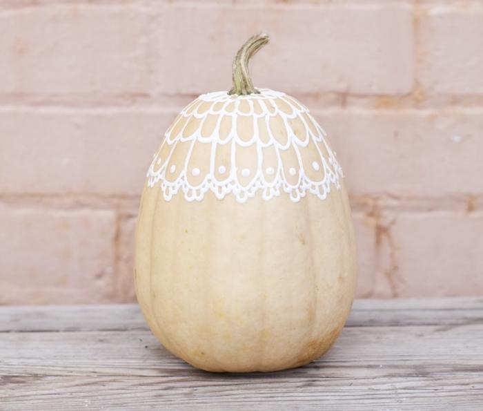 déco simple sur une citrouille blanche aux lignes géométriques en peinture blanche, modèle citrouille décorée