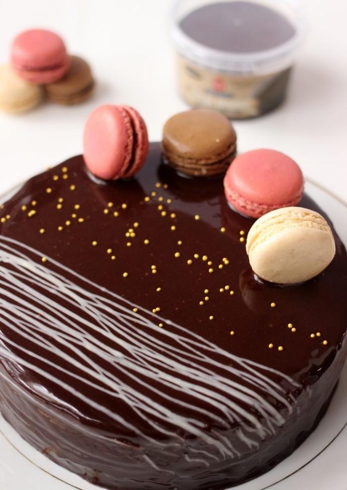 recette de gâteau au glacage miroir chocolat, décoré de macarons vanille et fraise