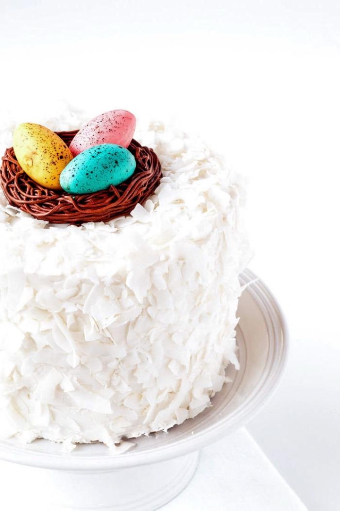 glacage gateau simple à la noix de coco et crème au beurre pour une belle finition d'un gâteau à la noix de coco, gâteau de pâques au glaçage à la crème au beurre et aux flocons de noix de coco, décoré avec un nid d'oeufs