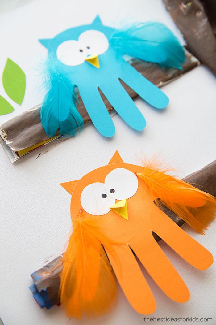 empreintes de main façon hibou aux ailes de plumes colorées, des yeux et bec en papier sur une bande de papier marron