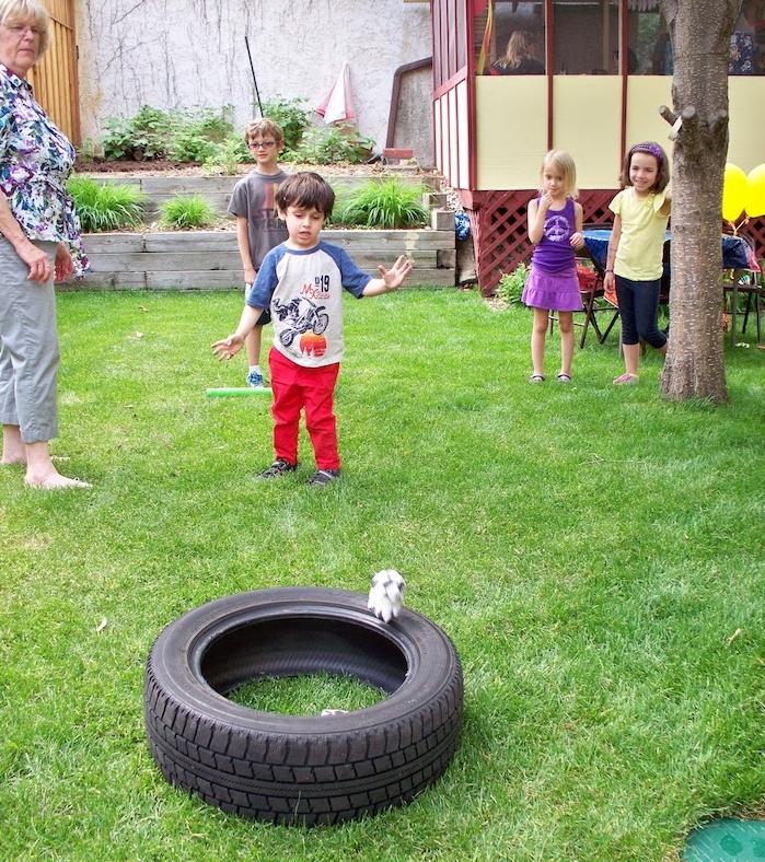 exemple de jeu d adresse enfant, lancer un objet dans un pneu creux à distance, idée d activité anniversaire enfant amusante
