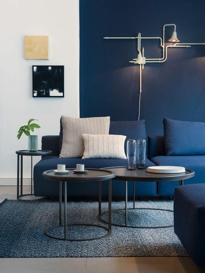 sofa bleu, couleur mur salon bleu, tables rondes noires, décor contemporain avec deux peintures de salon