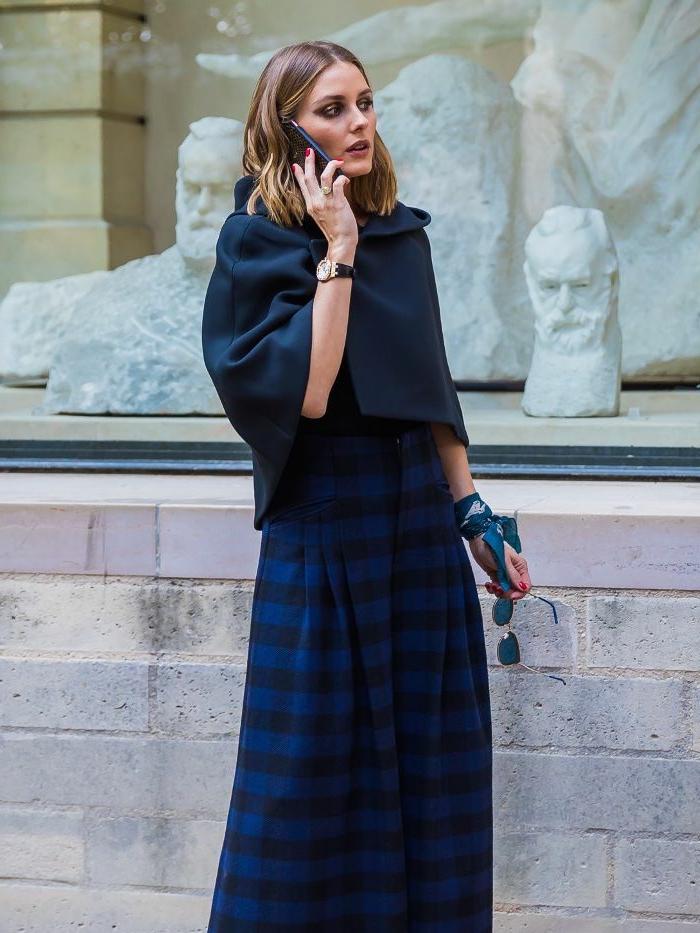 Olivia Palermo avec une tenue élégante bleue, jupe longue plissée et gilet d'automne