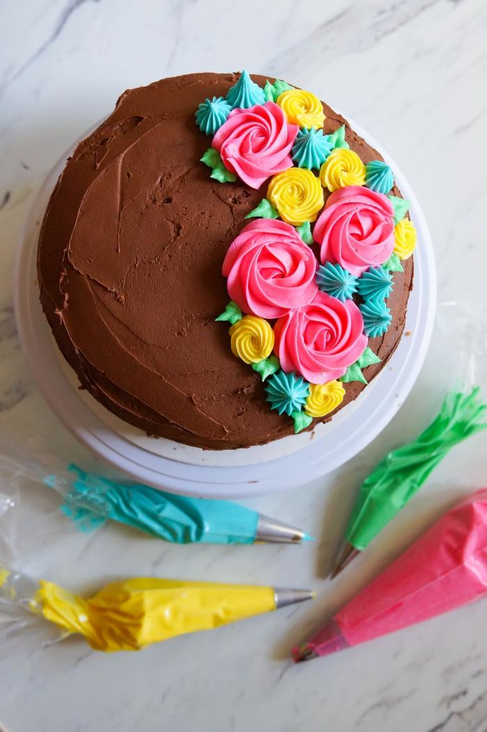 un simple gâteau recouvert de nappage au chocolat, décoré avec des fleurs au glacage sucre glace et beurre coloré réalisées à la poche à douille