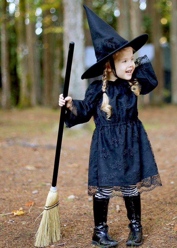 deguisement de sorciere pour petite fille, robe noire dentelle, chapeau de sorciere, tresses enfant fille, bottes noires, balai