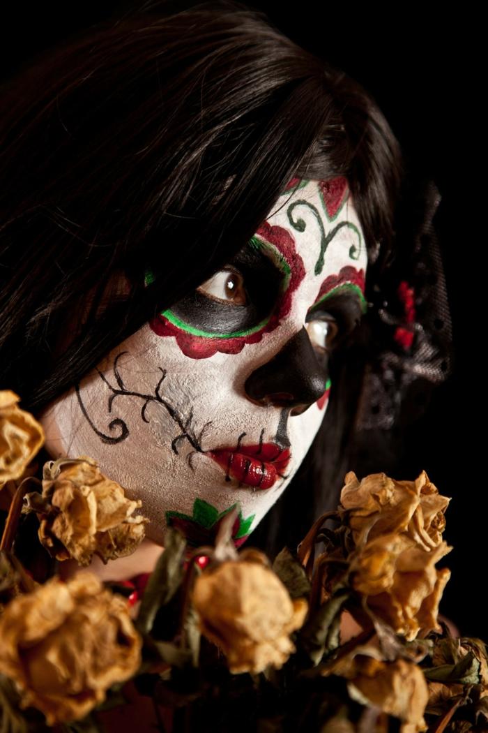 déguisement pour la fête des morts, grandes orbites peintes, nez peint noir, lèvres rouges, fleurs sèches