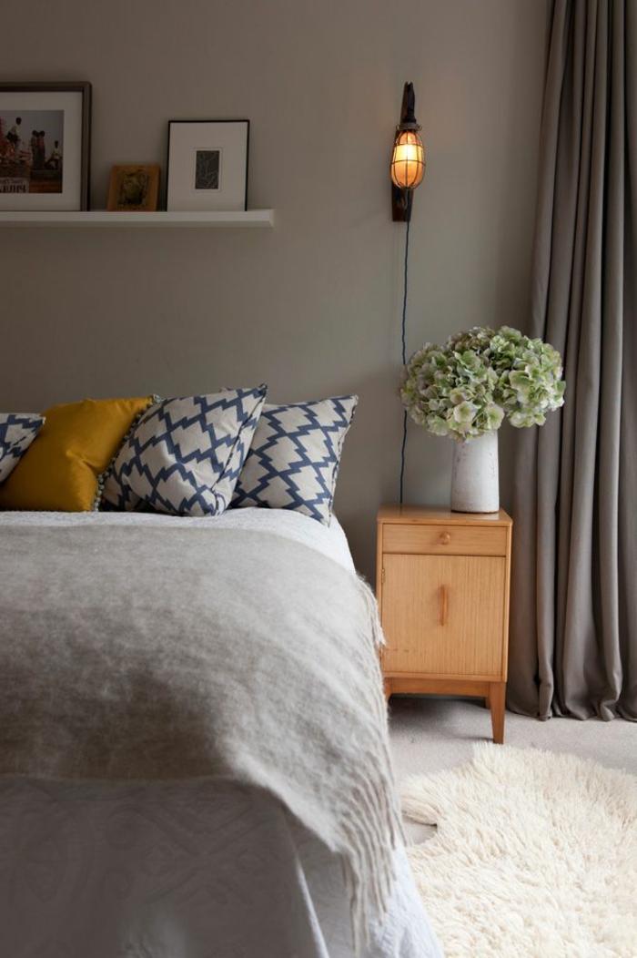 deco cocooning chambre, coussins géométriques, applique murale cage, grand bouquet de fleurs blanches, chevet en bois