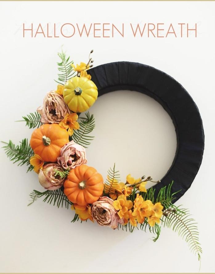 couronne de halloween en cerceau en bande noire avec decoration de potirons décoratifs, fleurs d automne et feuilles