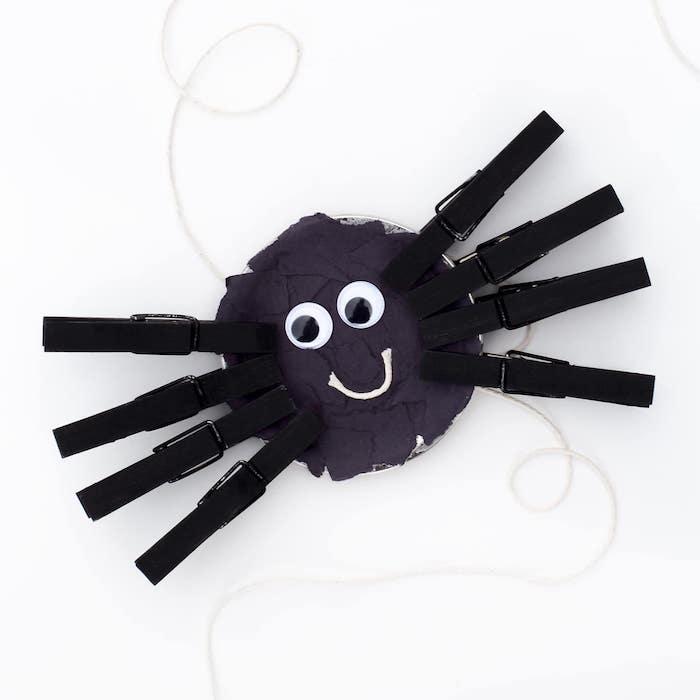 bricolage halloween maternelle, araignée en assiette de papier décorée de bouts de papier noir, pinces à linge repeints en noir et des yeux mobiles