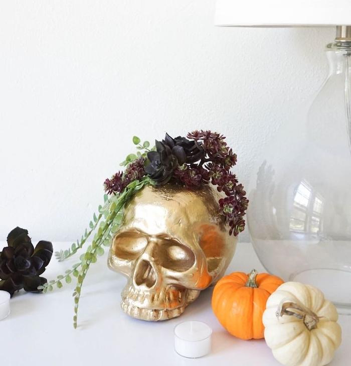 crâne décorative couleur or avec decoration de plantes, entourée de potirons décoratifs, bougie et fleur artificielle noire