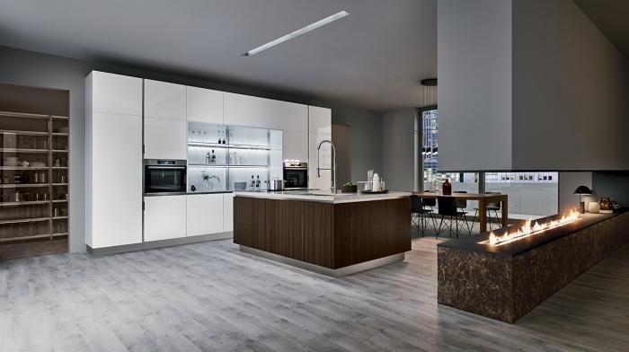 ambiance stylée et moderne dans une cuisine ouverte vers le salon avec îlot central en inox et bois foncé équipé d'évier