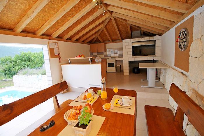 terrasse couverte en bois sur carrelage avec murs en pierres et cuisine d'été, bancs et table en bois au bord de la piscine