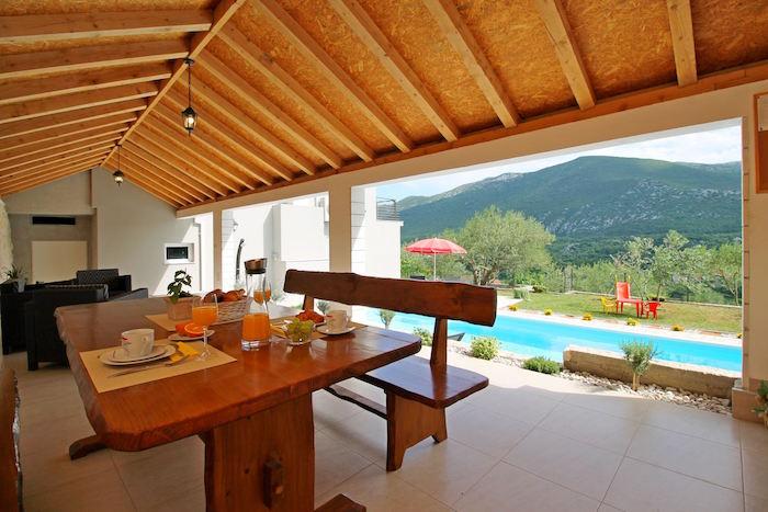 terrasse couverte en bois avec table et banc rustique dans maison avec piscine et vue sur montagne