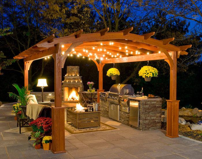 cuisine d'été extérieure en pierre sur terrasse avec pergola en bois et cheminée