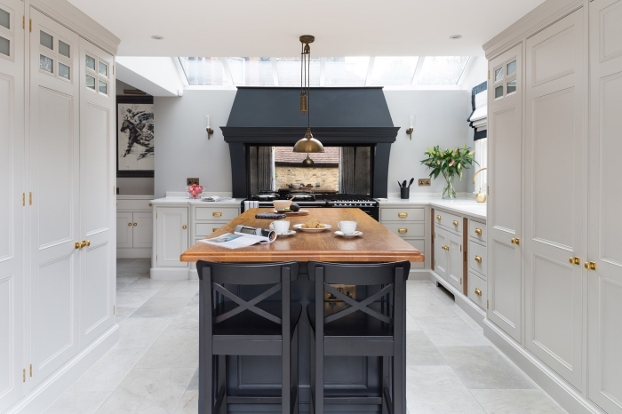 idée déco traditionnelle avec accents modernes dans une cuisine blanc et noir avec éléments en or et bois