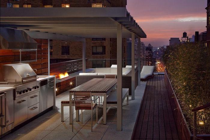 cuisine d'été couverte en extérieur sur balcon appartement avec salon canapé et matériel inox