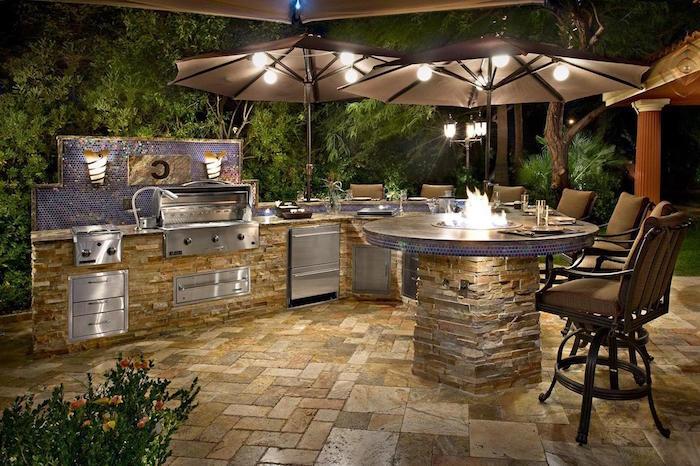 cuisine d'été extérieure sur terrasse avec carrelage table et plan de travail et parasol lumineux