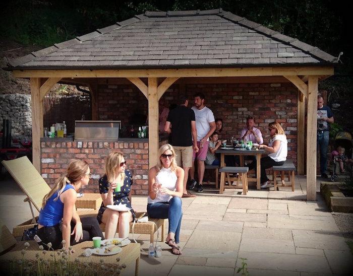 abris en bois et briques avec cuisine équipée et table à manger pour jardin
