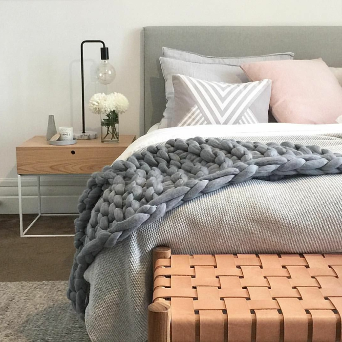 plaid gris au tricot, banquette de lit tressée, petit chevet en bois, lampe design industriel, déco chambre cocooning
