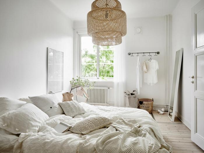 deco cocooning dans la chambre, plafonnier en rotin, grand lit blanc avec plusieurs coussins, sol de planches, miroir adossé