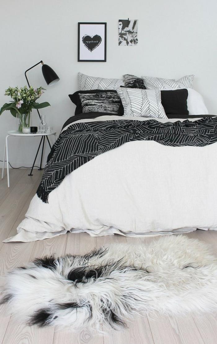 lit blanc et gris, table de chevet blanche, tapis fourrure, cadre peintures, sol en planches de bois, peinture murale couleur claire