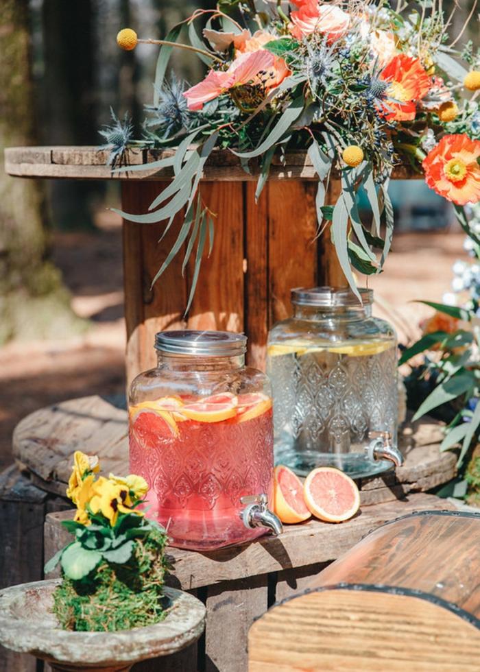 boissons rafraîchissantes pour les invités d'un mariage theme champetre, tronc de bois, bouquet de fleurs sauvages