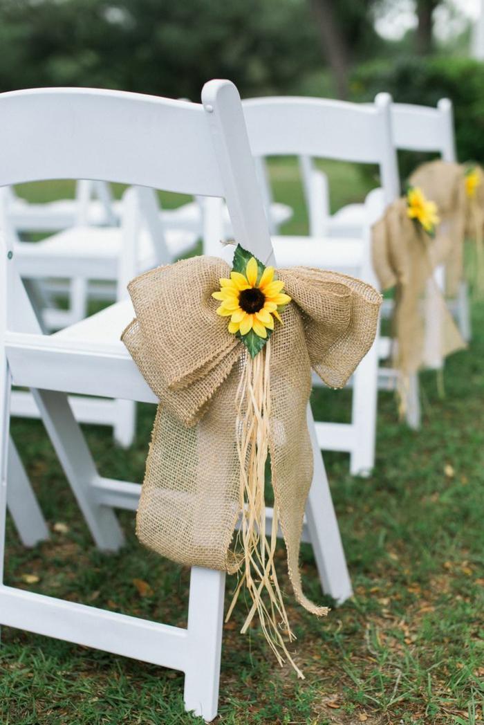 mariage campagnard qui se déroule en plein air, chaises blanches, rubans de jute décorés de tournesols