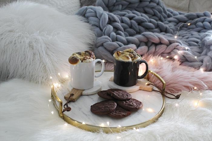 ambiance cocooning, plateau en bois et métal, cookies et cupcakes, fausse fourrure rose, plaid gris au tricot