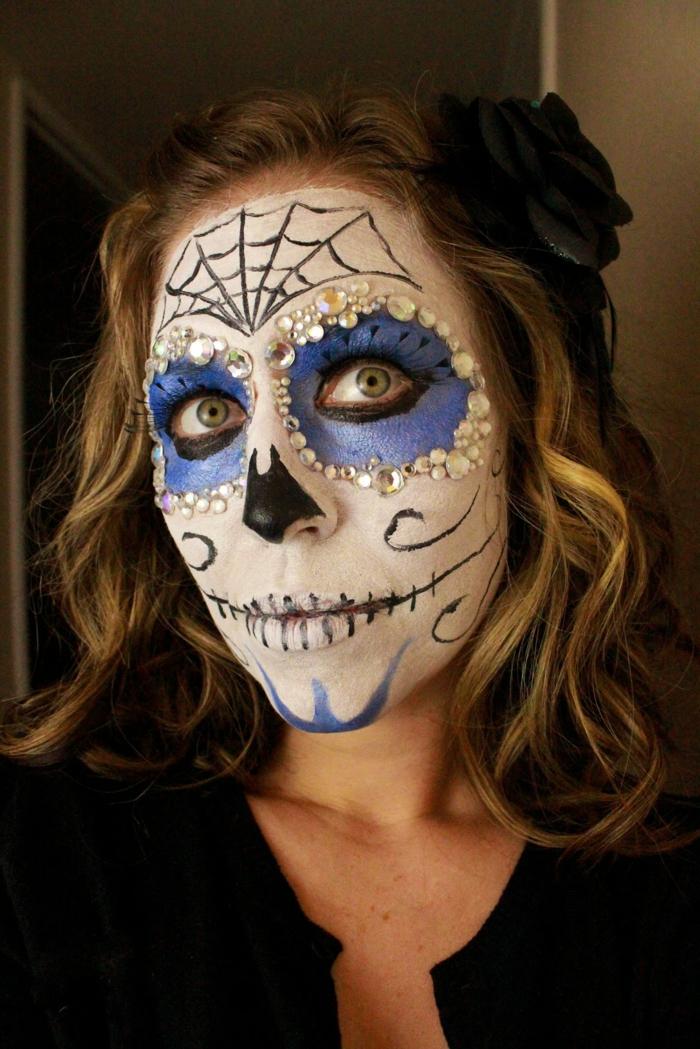 sourire de squelette, toile d'arraignée, pointe du nez noire, orbites des yeux bleus, strass, fleur noire