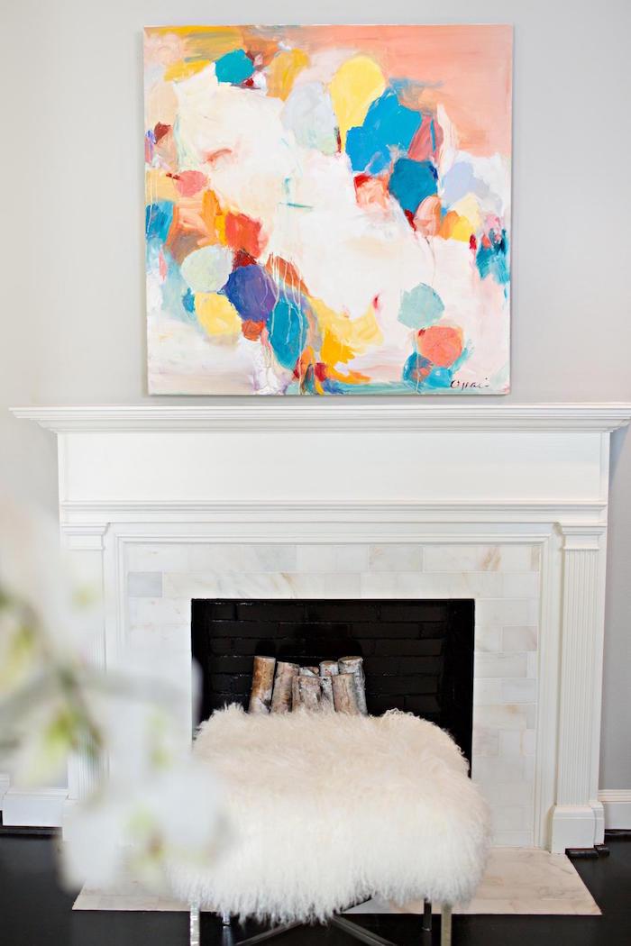 déco cheminée minimaliste avec manteau blanc et credence marbré sur mur blanc et cadre coloré abstrait