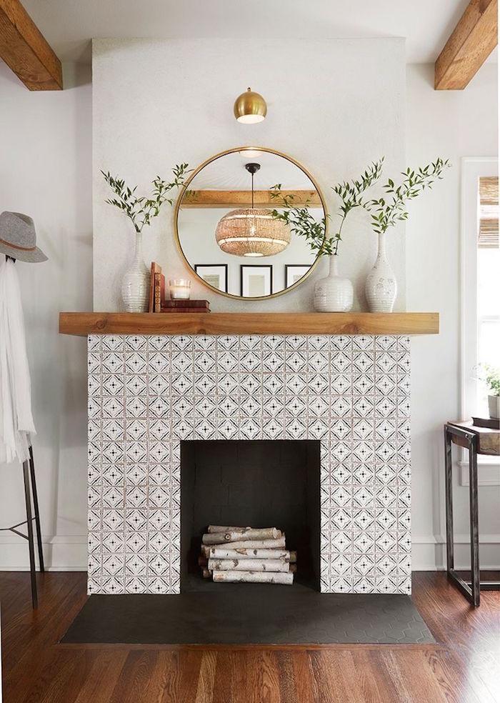 photo décoration de salon sur parquet avec manteau de cheminée déco en mosaique type crédence blanche, support en bois avec vases et miroir rond doré