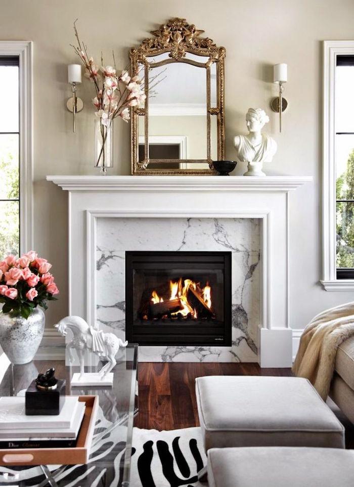 manteau de cheminee blanc classique avec cadre marbre blanc gris, salon avec mur blanc cassé, sol parquet foncé, objets déco avec statuette et miroir doré vintage