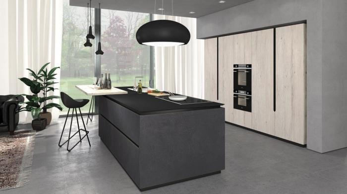 grande cuisine ouverte vers le salon avec murs en béton et îlot central en gris anthracite équipé de plaque cuisson et d'évier