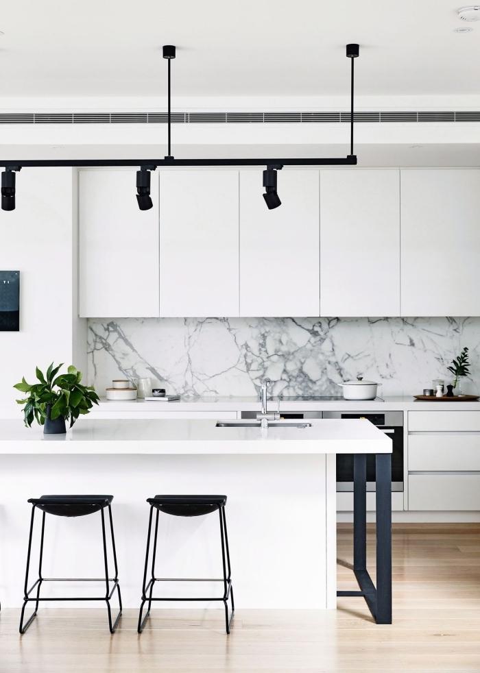 modèle de cuisine blanche avec parquet bois clair et crédence marbre à déco avec accessoires en noir mate
