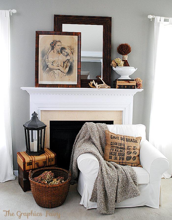 coin cheminée dans salon avec objets déco retro avec valises anciennes panier et cadres anciens, fauteuil ikea blanc en tissu