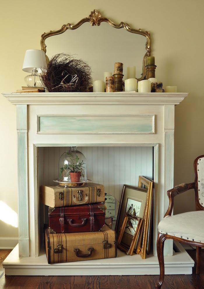 manteau de cheminée décoratif blanc patiné bleu vintage avec objets déco mini vieilles valises cadres et collection de bougies
