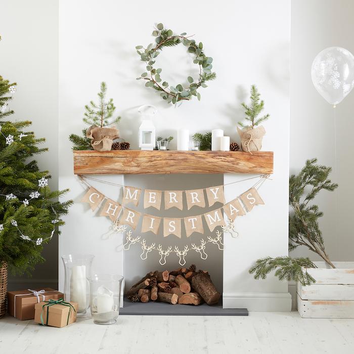emplacement cheminée dans mur blanc avec décoration de noel minimaliste avec guirlande merry christmas sous poutre en bois, branches de pin dans caisse en bois déco vintage et couronne de feuilles sur le mur