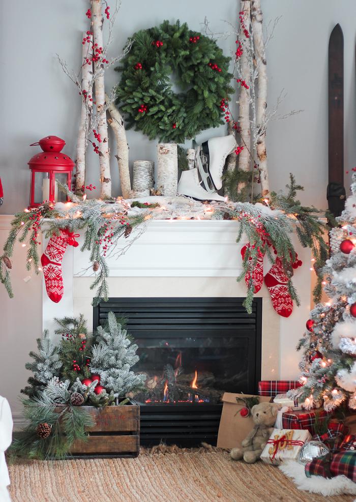 modele cheminée avec deco de noel et accessoires comme chaussettes rouges, branches bois, couronne gui sur le mur gris, sapin, caisse en bois déco
