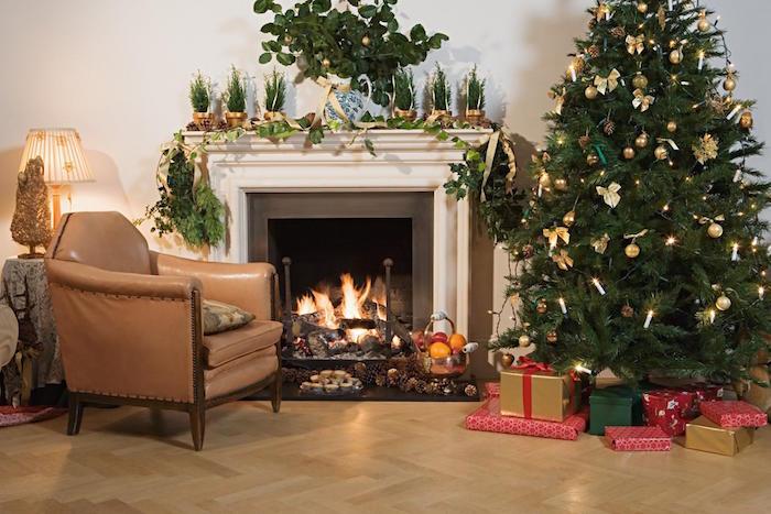 cheminée dans salon sur parquet flottant ou lino, fauteuil en cuir ancien et décoration de noel avec sapin, mini pins et différentes plantes vertes d'hiver