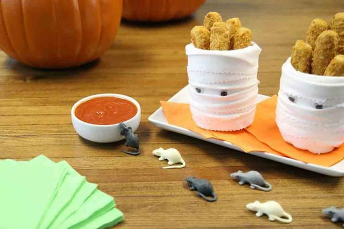 un buffet d'halloween effrayant avec des pots momies de bâtonnets de fromage
